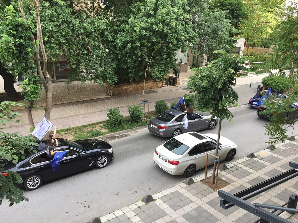 Liikennettä Istanbulissa Fenerbahçessa Aasian puolella. Nuoret heiluttavat lippuja autoista.