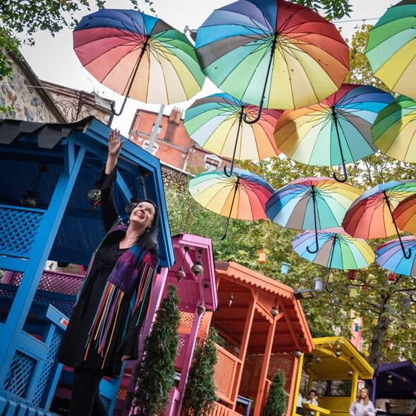 Seven Hills Sagan Anne kurottaa kohti värikkäitä sateenvarjoja ja hymyilee