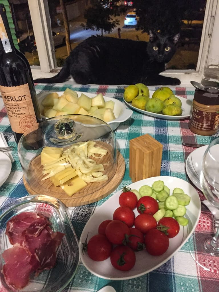 Musta kissa pöydällä vieressään paljon ruokia