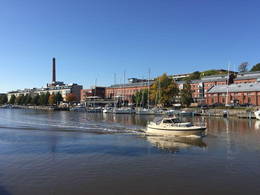 A boat sailing in Aura river in Turku in daytime