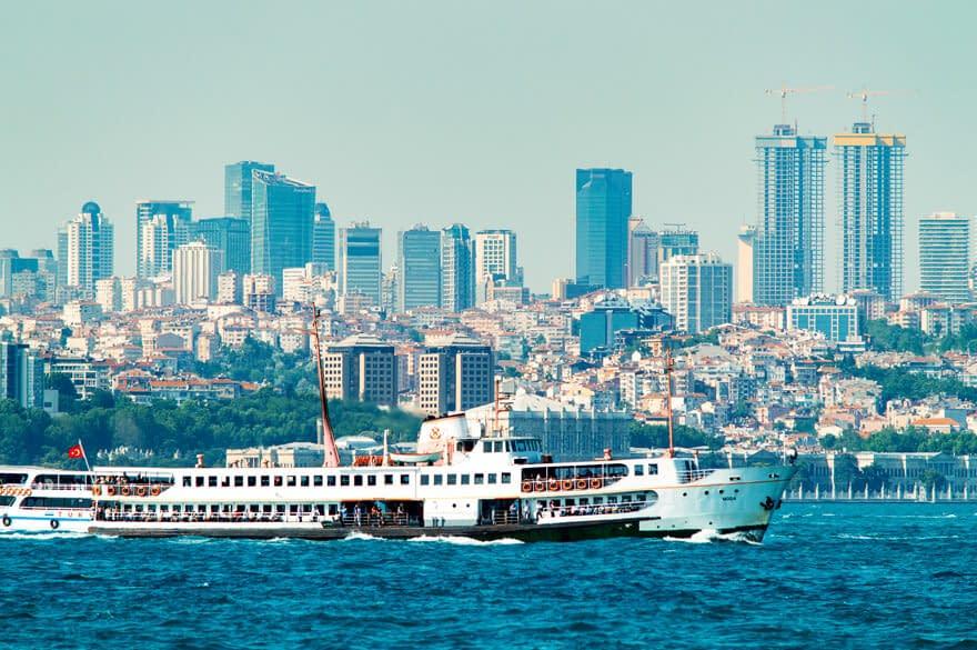 Suuri lautta kulkee Bosporinsalmella taustallaa Leventin liikekaupunginosa Istanbulissa